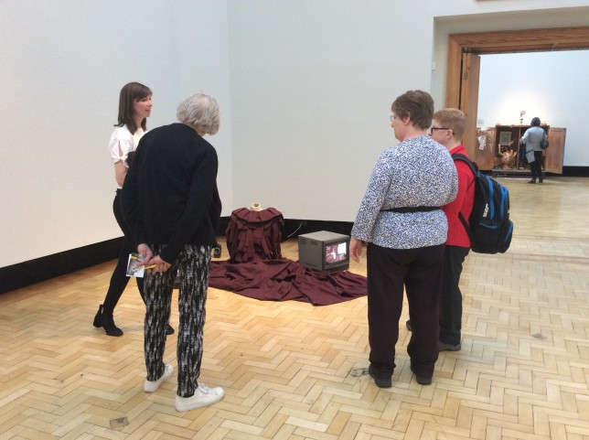 The group looking at Ruth Barker's installation for her performance The Foot Exerts Pressure on the Surface of the Glass. Dress by Lesley Hepburn. (Credit: Alice)