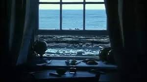 A window, half-open, half-shut. The writing desk within, the untamed, restless sea beyond.