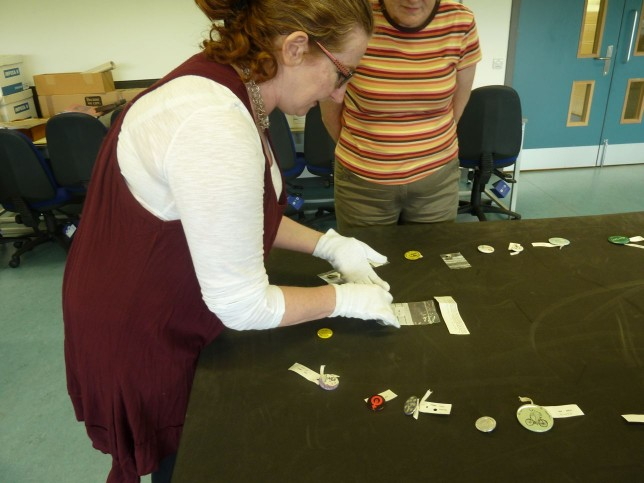 Fiona Hayes, Social History Curator, with the badges from GMRC's collection.