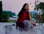 Evening, and Salma sits on the roof of her village home when she revisits it for the filming of the documentary.