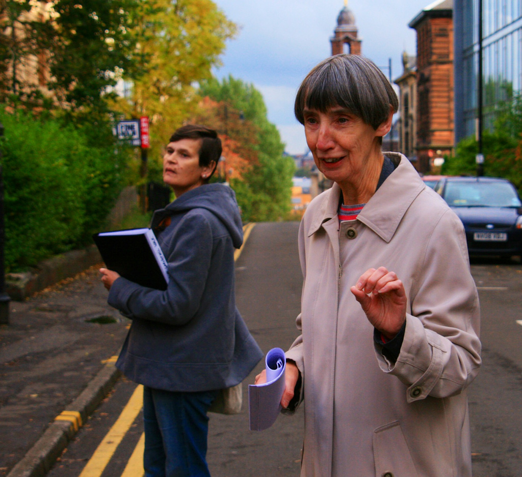 Colour photo of guides Joyce and Esther, standing on a leafy street with red sandstone building in the background. Esther is turned towards the camera, sharing information with a group of people who are out of sight.