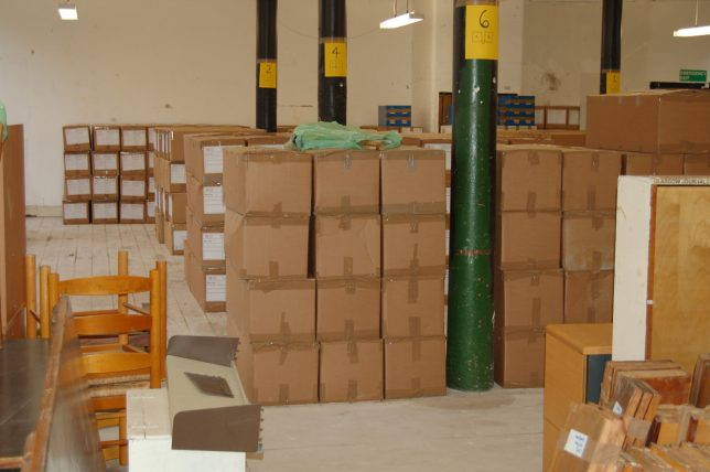GWL Collections being moved into temporary storage at 81 Parnie St, a large space with solid green columns, and metre-long cardboard boxes stacked up in columns of three by four boxes