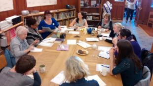 Women around a table in GWL participating in a writing workshop