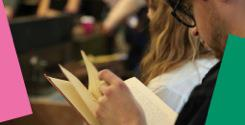 Close up photo of people standing in a room reading books.
