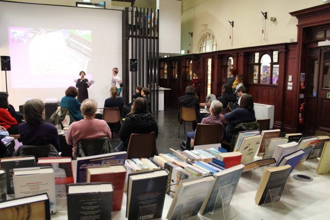 Spring Programme Launch 2017. A woman speaks in front of a group of seated people and here is a book sale taking place in the foreground.