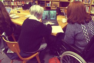 Louisina and Claire working together on a laptop
