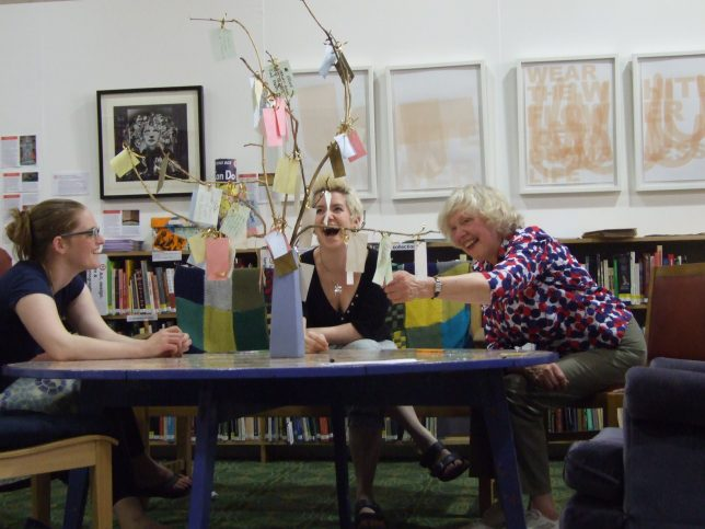 "Three volunteers sitting round a table laughing while reading messages on a ""sharing tree"""
