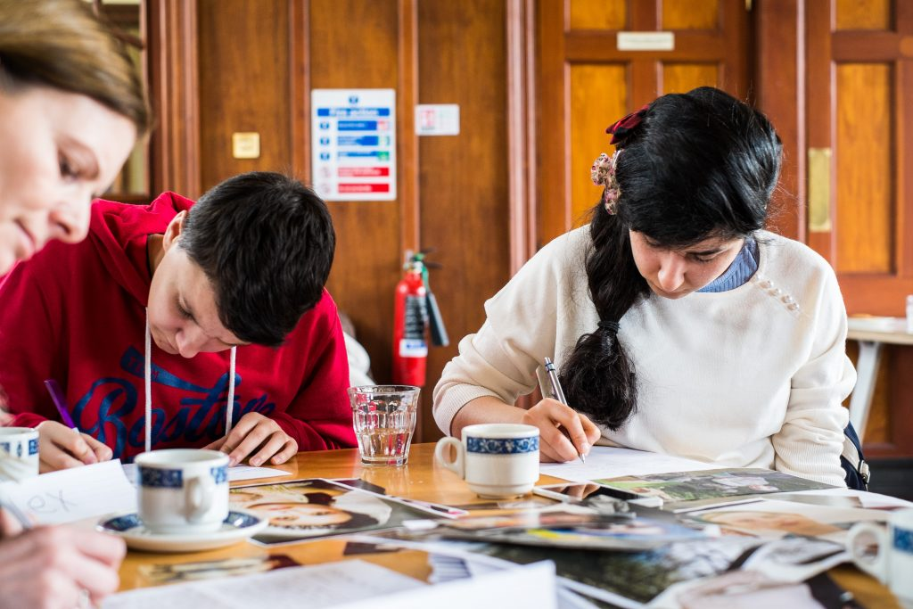 A small group sit round a table writing. Everyone has their heads down and looks to be focused. There are tea cups and what look to be photographic prompts on the table.