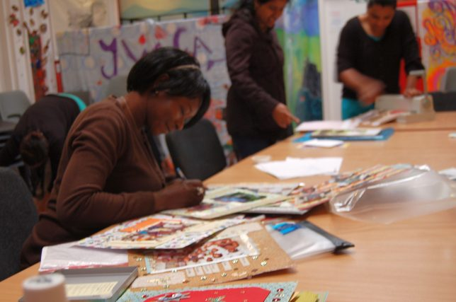 Three women sit around a table full of craft supplies making cards and badges. There are shelves full of books in the background.