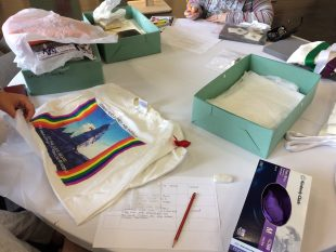 A tshirt from the Lesbian Archive on a table with archive boxes and pieces of paper