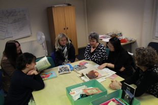 A group of women looking at the mini archive of GWL in Dundee