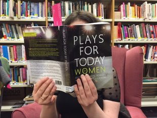 Photograph of person reading a book entitled 'Plays for Today: Women'. The person is sitting in a cosy chair in GWL with shelves of books visible in the background.