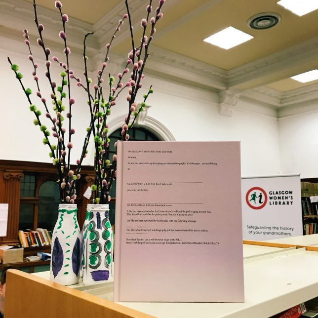 Photograph of new publication sitting on the top of GWL shelves beside decorations in the suffragette colours, purple, green and white. The publication is quite a large hard back book in a soft pink colour.