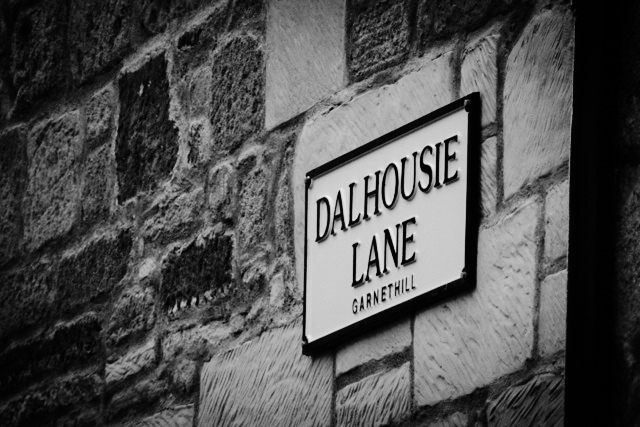 Close up black and white photograph of Dalhousie Lane street sign which is on a stone wall.