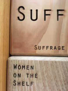 A close up of a wooden cube with 'SUFF' in large letters at the top and 'Suffrage' in smaller letters at the bottom. This block is sitting on top of a similar block which has the words 'Women on The Shelf' engraved into it.