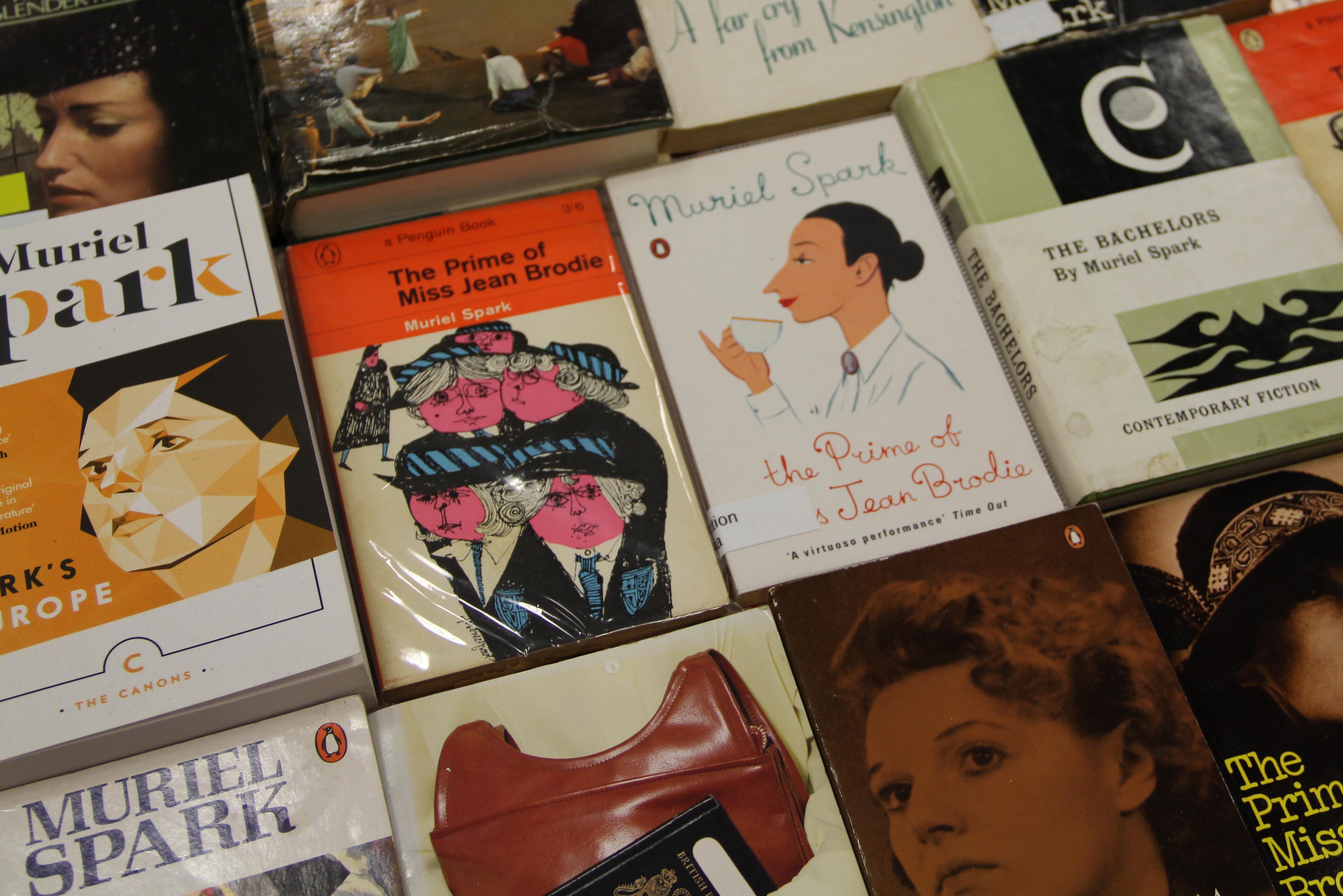 A dozen Muriel Spark novels lined up on a table show the range of cover imagery including bold graphics and illustrations, portrait photographs of Spark herself and more abstract designs.
