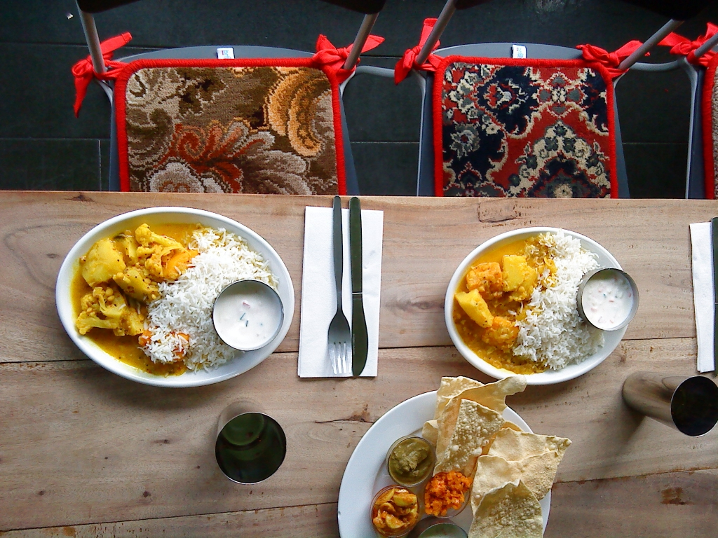Chairs with beautiful red, blue and gold patterned cushions are shown in the background with a table with plates of curry and rice in the foreground.