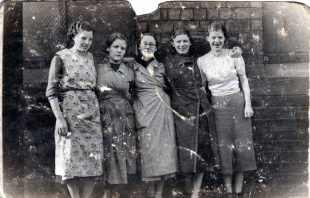 Black and white photo of a group of women standing with their arms around one another outside.