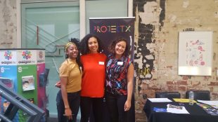 Photograph of three women of colour smiling and with their arms round one another. They are standing in front of a banner for 'Project X'.