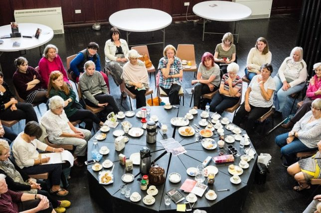 A large group of women sit round a big table covered with tea and food.