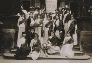 Black and white photograph of a group of suffragettes gathered on a set of stairs. Many of the suffragettes are wearing tartan sashes.