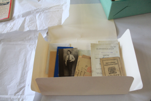 An open archive folder gives us a glimpse inside at some paper based materials. including an old black and white photograph of a women in uniform and a National Registration Identity document.