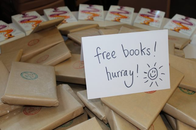 A big pile of books wrapped in brown paper with a handwritten label that says 'free books! hurray!' and has a line drawing of a smiling sun on it.