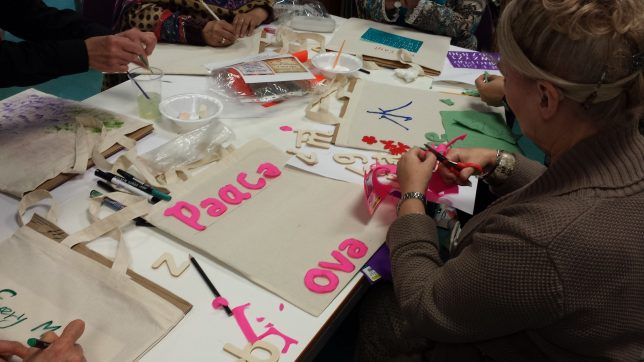 Women's hands making at a busy table, cutting out letters in pink and green to read 'Peace'.