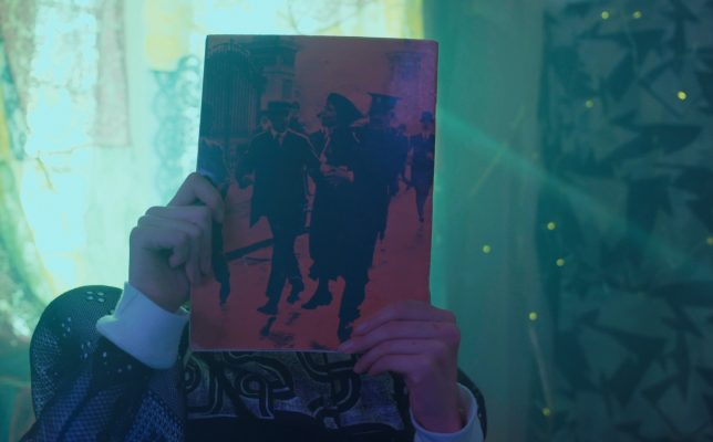 Image showing someone holding an old magazine in front of their face perhaps closely inspecting the cover or hiding. The room they are in has soft lighting with green tones from the curtains shining from behind them.