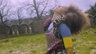 A woman leans her head back as if taking in the sunlight on her face or stretching back mid motion. There is an old stone wall in the background and she is in a field.