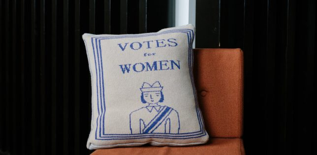 Donna Wilson's Book Cushion on a chair. The cushion has a knitted pattern with 'Votes for Women' above the image of a woman wearing a sash.