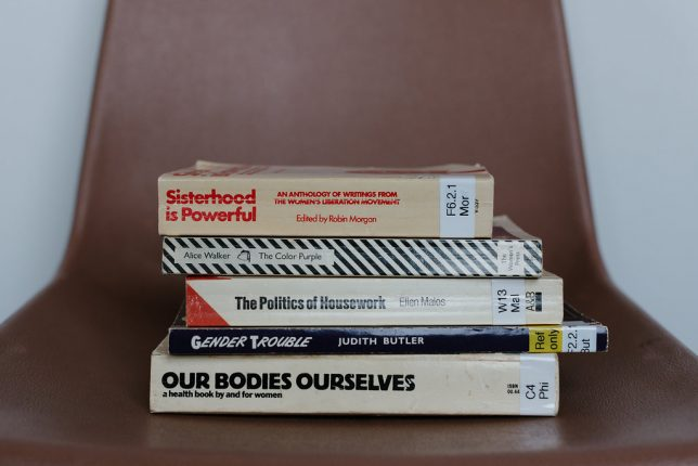 Image of a pile of books including 'Our Bodies Ourselves and 'The Politics of Housework'