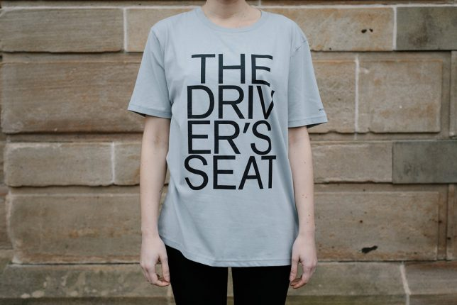 Grey t-shirt with 'The Driver's Seat' emblazoned on the front