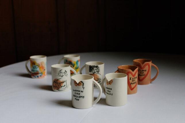 Slogan Mugs all displayed on a table