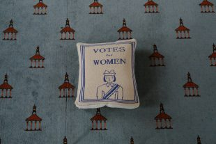 Image of a cushion embroidered with 'Votes for Women' above the image of a woman wearing a sash