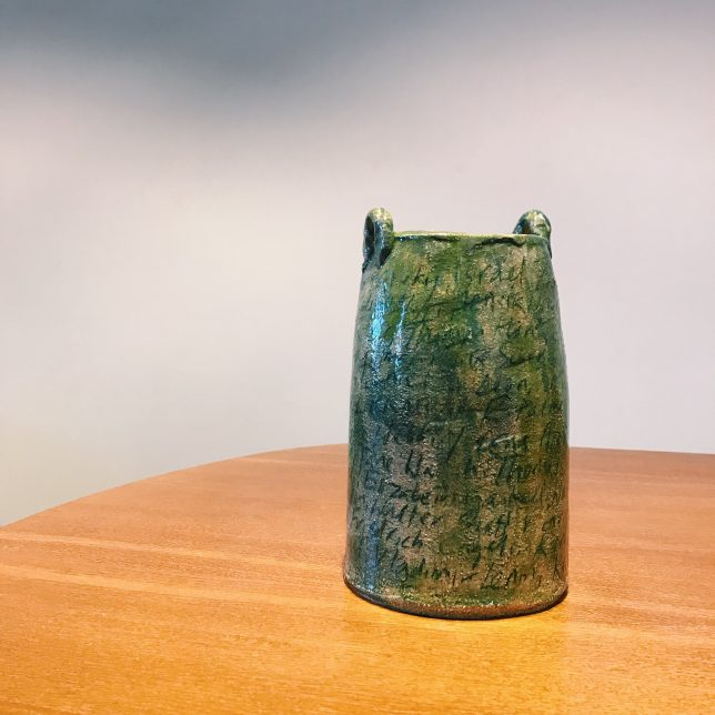 Photograph of one of Fiona Jack's ceramic pieces installed in the Our Red Aunt exhibition at GWL in 2018. The ceramic piece has a green and brown glaze and has names of authors inscribed into the surface. They aren't fully legible in the photograph but they inspired this blog post.