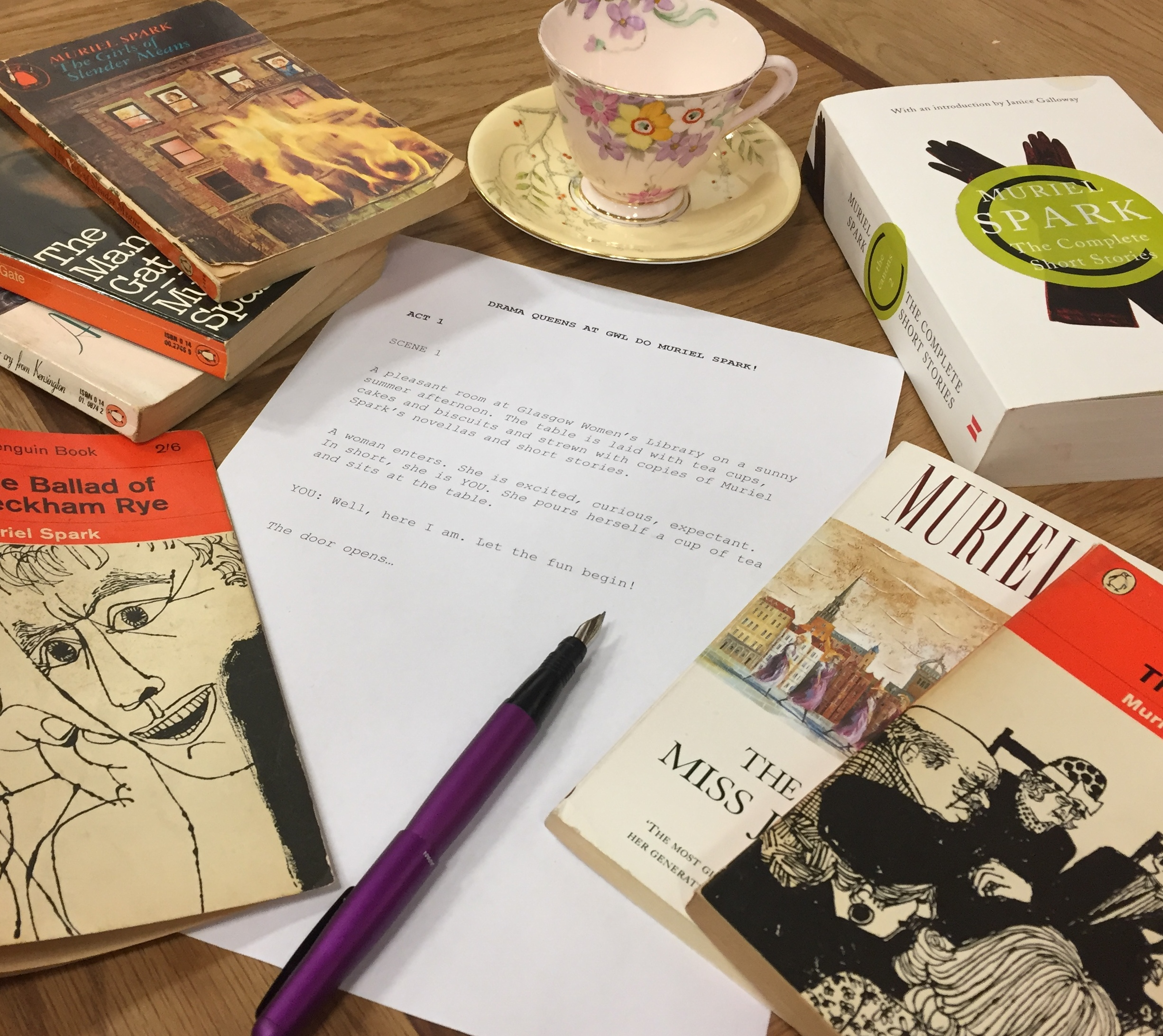 Photograph of a table of Muriel Spark novels surrounding a piece of paper with the beginnings of a script written about a women coming to the library for Drama Queens.