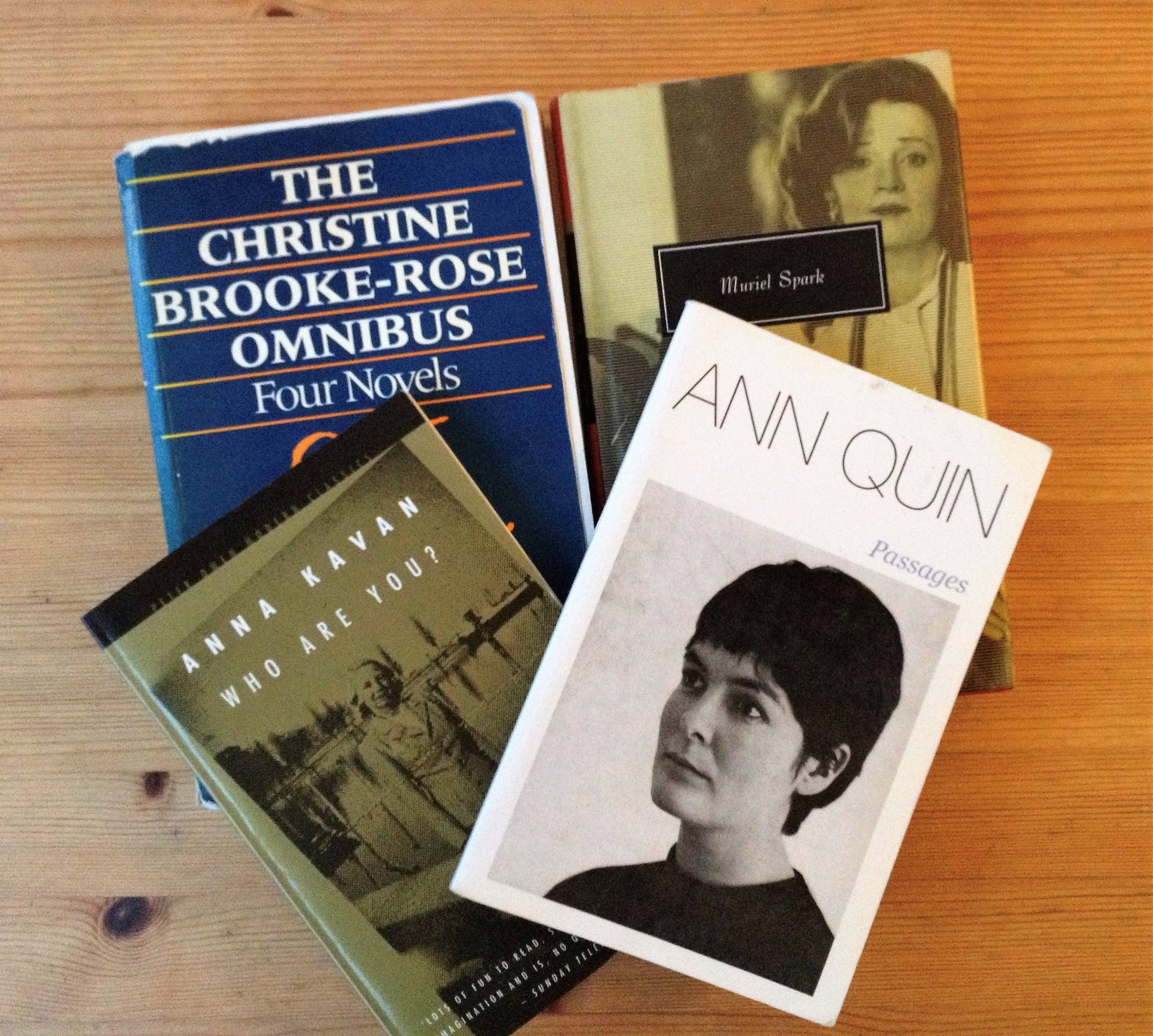 Four books are placed together on a table. Their covers show that books are by Christine Brooke-Rose, Anna Kavan, Ann Quin, and Muriel Spark. It is possible to tell that the Ann Quin book is 'Passages' and the Anna Kavan book is titled 'Who Are You?'.