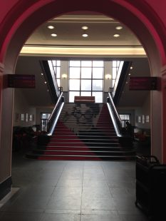 Photo taken from the bottom of the stairs in the National Library of Scotland. They are a wide set of stairs which have a vinyl covering that creates a portrait of Muriel Spark.