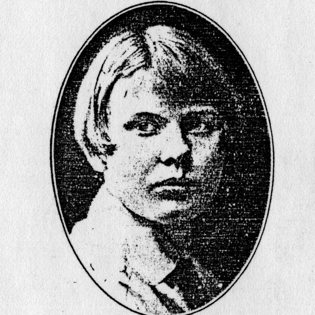 Black and white oval portrait image of a woman with a short haircut, looking slightly left of the camera. She is not smiling.