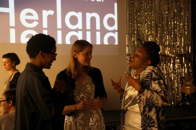 Three women stand in front of a projection that says 'Herland'. They are talking animatedly and look happy
