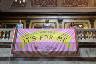 Three woman standing holding a flag that drapes over a marble balcony. The flag is pink with a yellow banner and the words 'Glasgow Women's Library' and 'It's for me' are written on the flag.