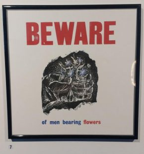 A framed print with a central image of a hand holding some blue flowers. The text above the image reads BEWARE in red capital letters; the text below reads 'of men bearing flowers', in blue and red font. The quote is from Muriel Spark's autobiography, Curriculum Vitae.