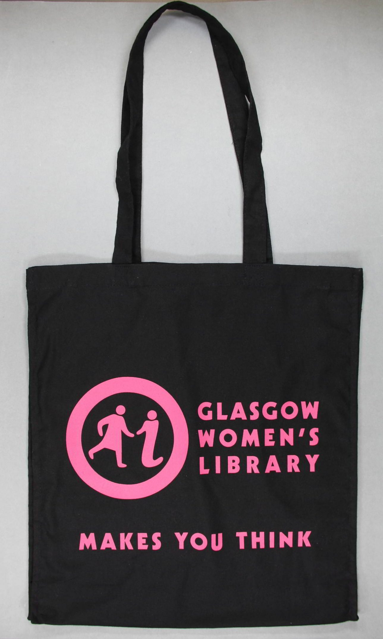 Black tote bag with bright pink text on it. It says 'Glasgow Women's Library' and 'Makes You Think' on it.