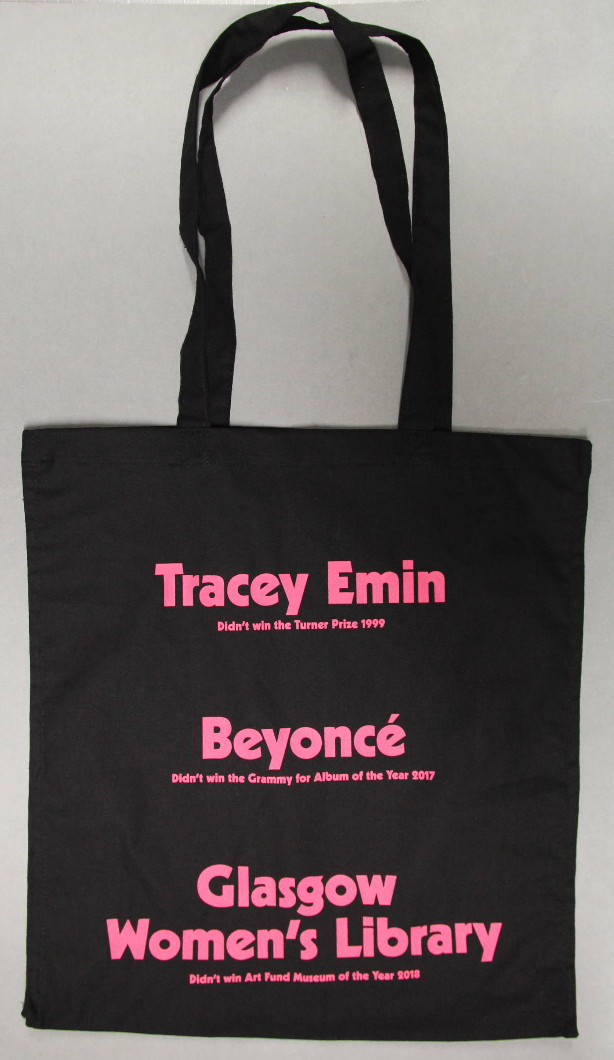 Black bag with bright pink text. The text reads 'Tracey Emin' [in large letters] 'Didn't win the Turner Prize 1999' [In smaller writing]. The rest of the text echoes this style of a larger name and smaller text. 'Beyonce didn't win the Grammy for album of the year 2017' and 'Glasgow Women's Library didn't win Art Fund Museum of the Year 2018'