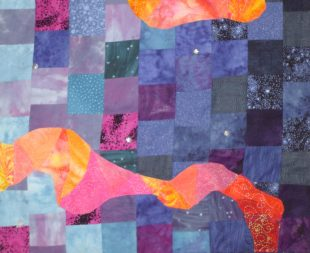 A patchwork quilt which has lots of squares of blues and purples. There is also a warm red and orange shape that wiggles from the bottom right to the middle left of the quilt.