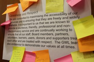 "A laminated A3 sheet with the definition of ""Openness and Respect"" with colourful postits around on on which volunteers have writing their values."