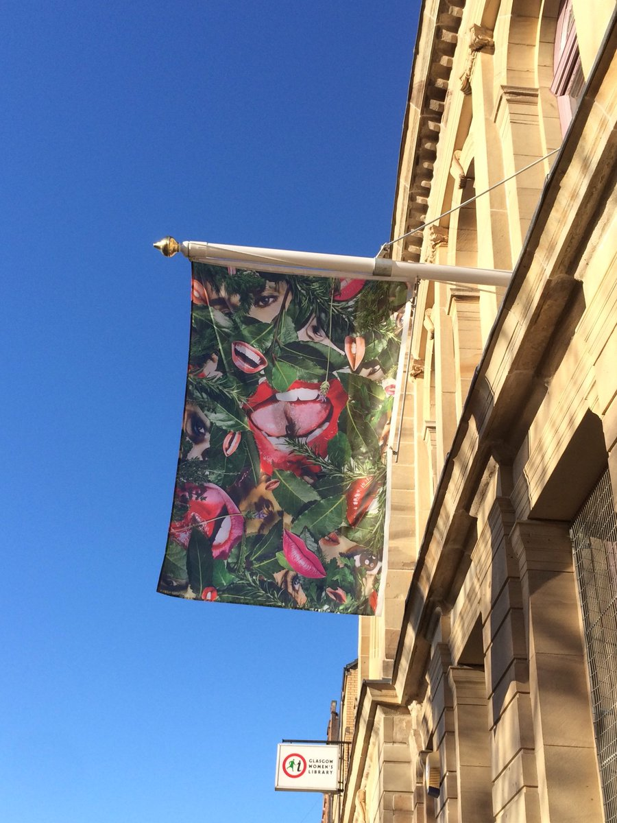 Linder's flag for Bower of bliss flying outside Glasgow Women's Library against a blue sky. The flag is a collage of bright pink mouths set in foliage like flowers.