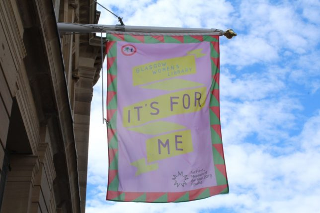 Flag designed by Visual Communication Resident (2018) Jyni Ong for our Art Fund Museum of the Year public engagement - on a pink background with a bold red and green border, a twisting yellow ribbon reads: Glasgow Women's Library: It's For Me