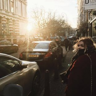 Photograph of Mhairi walking down the busy streets of Amsterdam, Netherlands. Mhairi is looking back into the camera. The sun is shining brightly into the camera reflecting the rays. Two cars are beside her parked.